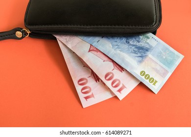 Black leather wallet with Taiwan new dollar bill on orange background, Taiwan Money (TWD)