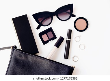 Black leather woman bag open out with cosmetics, accessories. Flat lay fashion beauty product concept