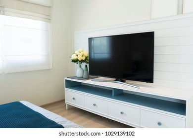 Black LED TV screen on wood cabinet in bed room