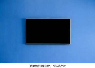 Black LED tv television screen mockup / mock up, blank on blue wall background in room for interior decoration design