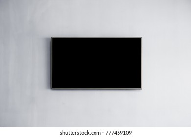 Black LED tv television screen mockup / mock up, blank on white wall background in room for interior decoration design