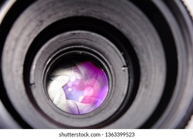 Black lens located on a white background. Multi-colored lights reflected in the lens near diaphragm and lens petals. Shutter concept, creativity, art in photography. Main equipment of the photographer
