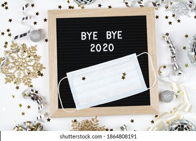 black letter board with text BYE BYE 2020 with decoration and mask on white background. Top view. flat lay New Year Christmas minimal background