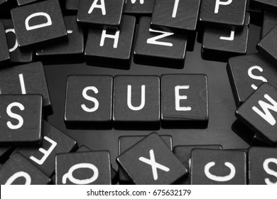 """Black letter tiles spelling the word """"sue"""" on a reflective background"""