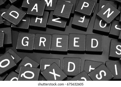 """Black letter tiles spelling the word """"greed"""" on a reflective background"""