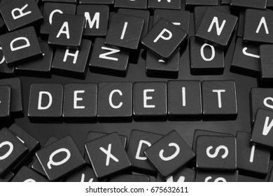 """Black letter tiles spelling the word """"deceit"""" on a reflective background"""