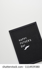 Black letterboard with white plastic letters with quote Happy Father's Day, on white background.