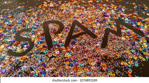 """Black lettering """"fingerpainted"""" into glitter and sequins pile. Spam concept. Not the food. Defocused. Copy Space."""