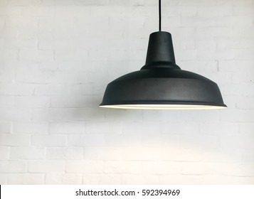 Black lighting fixture with white bricks wall background.