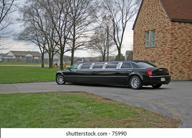 Black Limo with wedding party leaving for reception.
