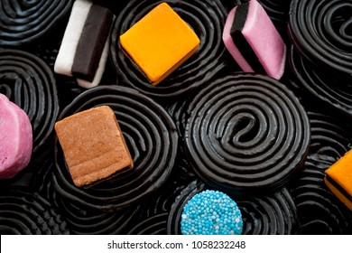 Black liquorice swirls, chewy candy and delicious dessert concept with macro close up on licorice wheels and other assorted licorice with a mix of colors and shapes