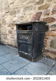 A black litter bin on a UK pavement with a cobbled stone wall to the rear