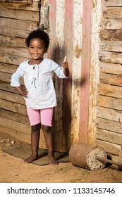 Black little girl showing a thumbs up while standing infront of a shack.