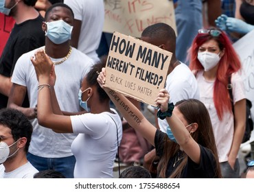 Black Lives Matter, Protest Against Racism in Memory of George Floyd. Sign Reading: 'How Many Weren't Filmed?' Masked Black Man, Woman and Red, Brown Haired White Women. ROME, ITALY - June 7, 2020