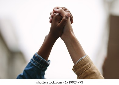 Black lives matter. Symbol of unity. Two women activists holding hands. Demonstrators protesting together holding hands.