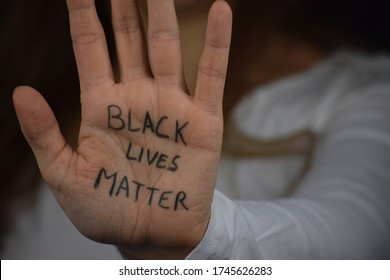 Black Lives Matter written on long haired white woman's hand. Caucasian girl  against racism and police brutality. Support to African Americans. - Shutterstock ID 1745626283