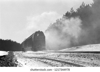 Black locomotive rides on railroad in winter forest on film. Train in cloud of hot steam. Old carriage. Atmospheric scanned analog photography with grain and scratch.
