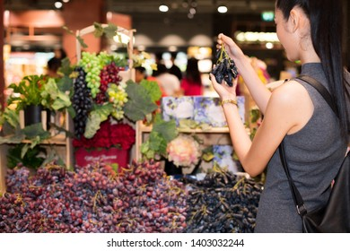 Black long hair adult Asian Woman in gray dress select pick up black grasp from bulk purple grasps rack from supermarket, selective focus. Concept decision making best choice from many good things