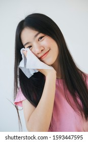 A black long hair woman raise the tissue paper touch her face and smile.