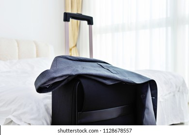 Black luggage in hotel room.