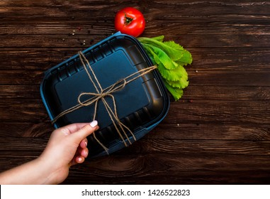 Black Lunch box tied with flagella. Food on dark brown wooden surface. Closed Box for food, tomato, cucumber and lettuce on the table. Healthy food. Place for text.