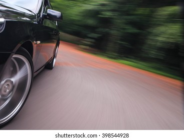 Black luxury sedan turning in forest.