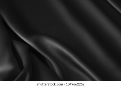 Black luxury wavy rippled glossy silk drapery cloth fabric. Abstract background