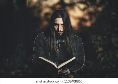 Black magician. A man with long hair. Cosplay Warlock. A creepy guy in a black robe