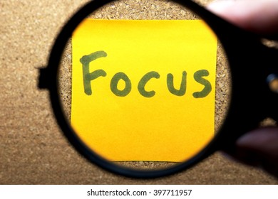 Black magnifying glass with Focus word on yellow sticky blank notes on cork bulletin/notice board.
