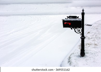 A black mailbox covered with fresh white snow