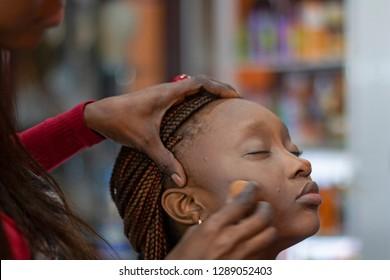 A black make up artist applying foundation on a beautiful black model face.