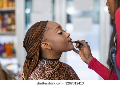 A black make up artist putting lipstick to a black model with pigtails.