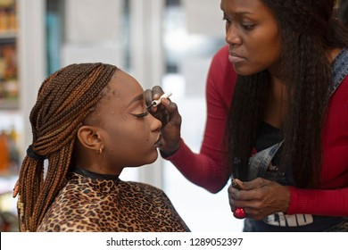 A black makeup artist apllying eyeliner on a beautiful black model.