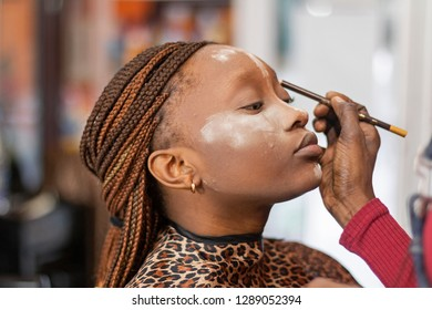 A black makeupartist drawing eyebrow on a beautiful black model.