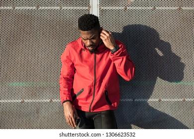 Black male athlete putting on earphones before outdoor urban training.