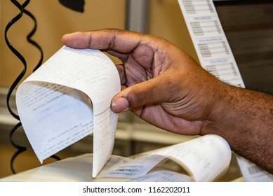 Black male cashiers hand taking sales slip from cash register with phone line hanging in background