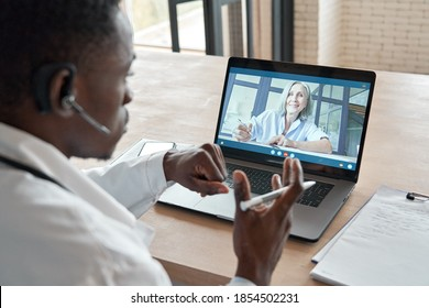 Black male doctor consulting senior old patient by telemedicine online video call. African physician using telehealth medical chat virtual healthcare appointment on laptop computer. Over shoulder view