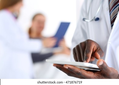 Black male doctor hand point with finger in digital tablet pc touch screen with patient lying in bad in background. Professional equipment, therapeutist ward round, search opportunities concept