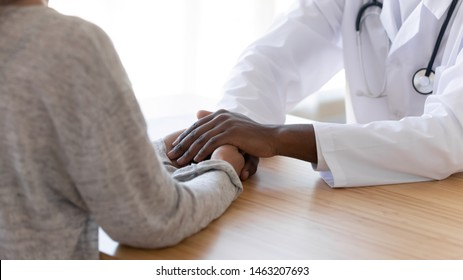 Black male doctor holding hands of female patient at meeting as women health medical care concept express trust support empathy about miscarriage, help hope in cancer disease therapy, close up view