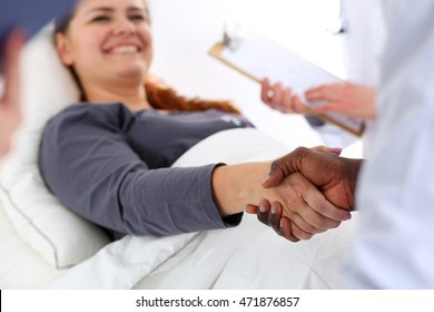 Black male doctor shake hands as hello with female patient lying in bed. Introduction or thanks gesture, welcoming friend, therapeutist ready to examine thankful client, tests advertisement concept