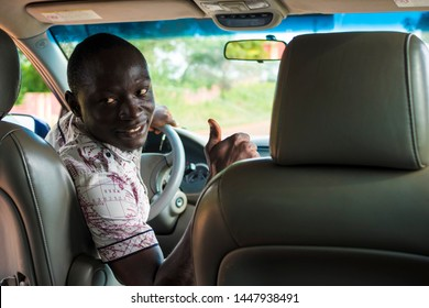 black male driver giving a thumbs up to people at the back of the car