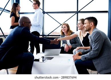 Black male executive sitting and shaking hands with white female colleague