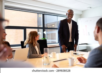 Black male executive standing and leading a work meeting in conference room