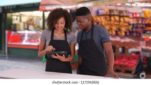 Black male and female waiter using digital tablet at London street market
