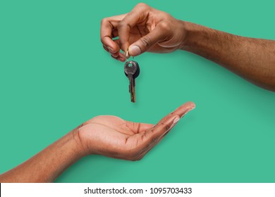 Black male hand holding new key and handing it over to another person on turquoise background