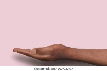 Black male hand at pink background with copy space. Empty palm of african-american man holding virtual object, asking or offering something. Conceptual mockup for ad, placard or motivation poster