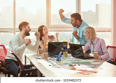 Black male leader reported good news, everyone is happy. Creative people designers extremely happy at messy desk in office.