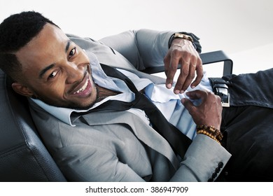 Black male lying on a chair with a suit on and lose tie and shirt smiling and looking very happy