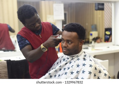 Black man in the african barbershop. Cute black man makes a haircut in the African salon. Hair style. Haircut by machine for adults.