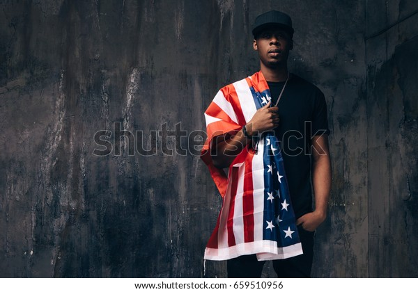 Black man with american flag on shoulder on dark background. Patriot, national event celebration, independence day, pride, immigration, us citizenship concept